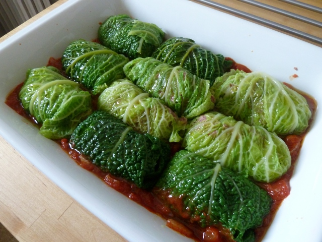 Étalez les feuilles de choux et déposez-y une boule de viande assaisonnée. Enroulez en finissant par rabattre les bords en dessous et disposez-les dans le plat.